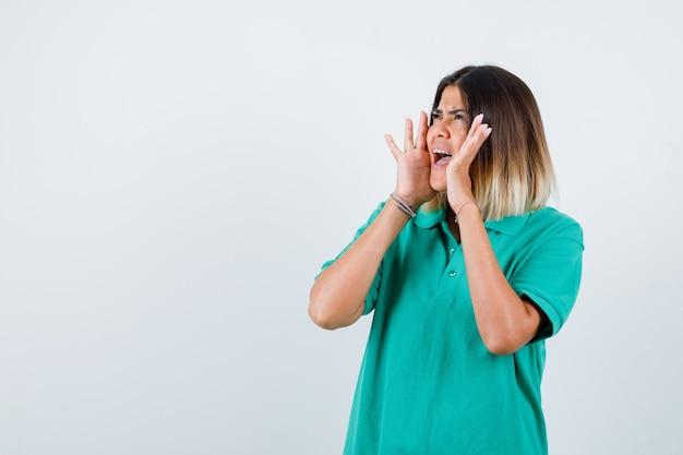 Jonge vrouw houdt handen in de buurt van mond in polo t-shirt en ziet er bang uit. vooraanzicht.