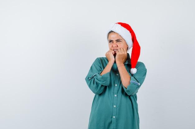 Jonge vrouw houdt handen in de buurt van mond in shirt, kerstmuts en ziet er doodsbang uit. vooraanzicht.