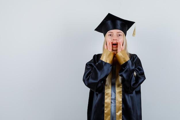 Jonge vrouw houdt handen in de buurt van mond terwijl ze geheim vertelt in afgestudeerd uniform