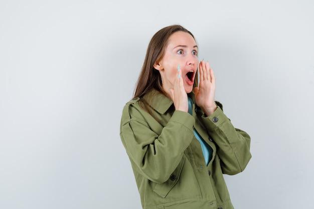 Jonge vrouw houdt handen in de buurt van open mond in groene jas en kijkt verbaasd. vooraanzicht.