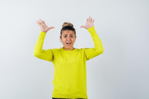 Jonge vrouw houdt handen op agressieve manier in trui, spijkerrok en kijkt geïrriteerd