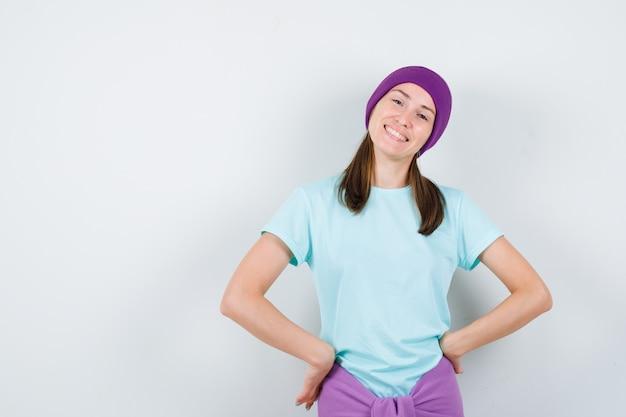 Jonge vrouw houdt handen op de heupen in t-shirt, muts en ziet er gelukkig uit. vooraanzicht.