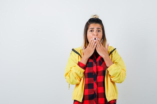 Jonge vrouw houdt handen op de mond in geruit hemd, jasje en kijkt geschokt. vooraanzicht.