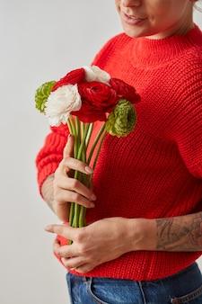 Jonge vrouw houdt in handen, kleurrijke bloemen van boterbloem op grijze achtergrond. als cadeau voor de vakantie