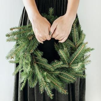Jonge vrouw houdt krans frame gemaakt van dennentakken. kerst samenstelling.