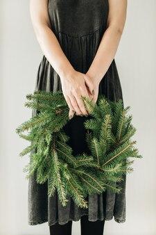 Jonge vrouw houdt krans frame gemaakt van dennentakken.