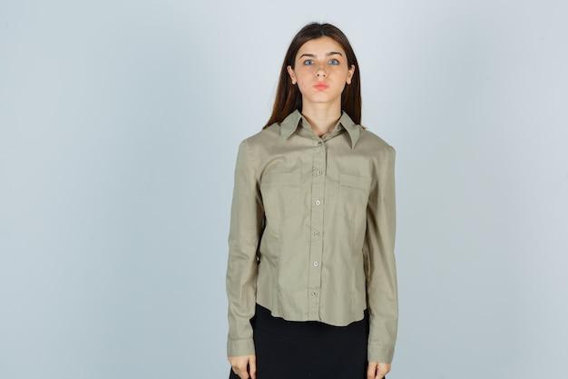 Jonge vrouw houdt lippen gevouwen in shirt, rok en kijkt verbaasd. vooraanzicht.