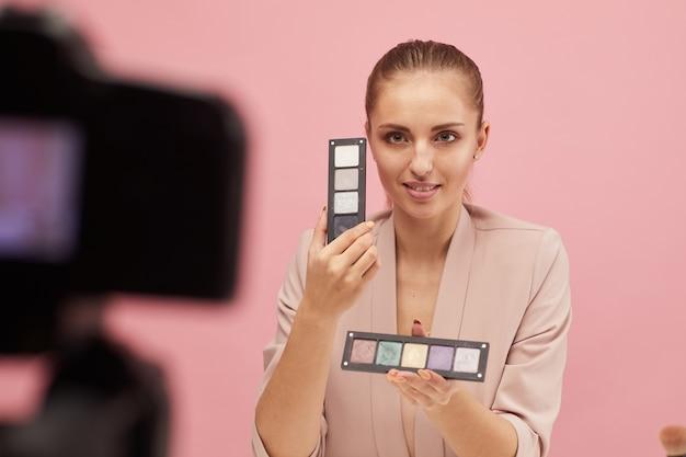 Jonge vrouw houdt oogschaduw in haar handen en toont ze aan de camera terwijl ze online met haar volgers praat