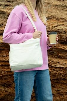 Jonge vrouw houdt stijlvolle eco tas en papieren beker buiten tegen grote zee steen