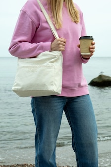 Jonge vrouw houdt stijlvolle eco tas en papieren beker tegen zee