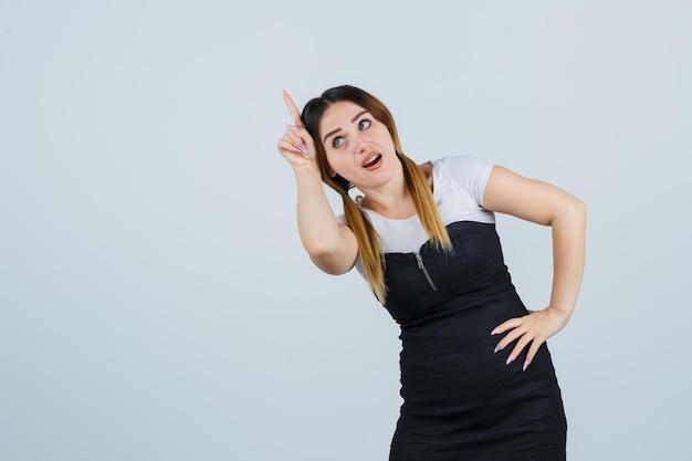 Jonge vrouw houdt vinger boven haar hoofd als hoorn