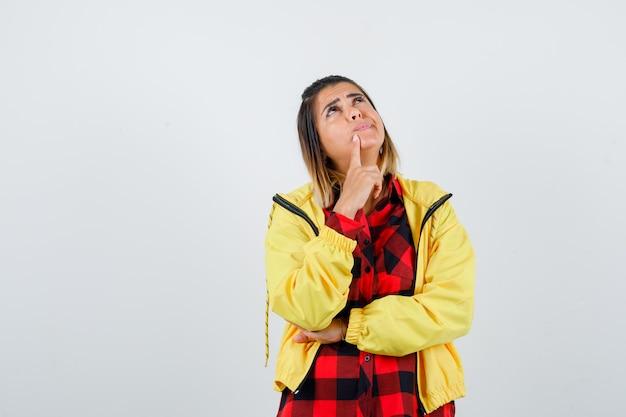 Jonge vrouw houdt vinger op kin, kijkt omhoog in geruit hemd, jas en kijkt peinzend, vooraanzicht.