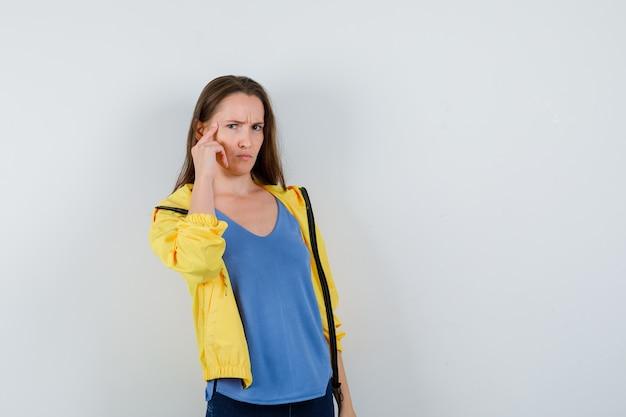 Jonge vrouw houdt vinger op tempels in t-shirt en ziet er intelligent uit. vooraanzicht.