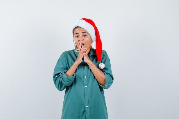 Jonge vrouw houdt vingers geklemd in shirt, kerstmuts en kijkt geschokt. vooraanzicht.