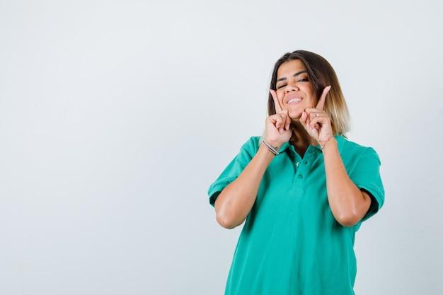 Jonge vrouw houdt vingers op de wangen in polo t-shirt en ziet er vrolijk uit, vooraanzicht.