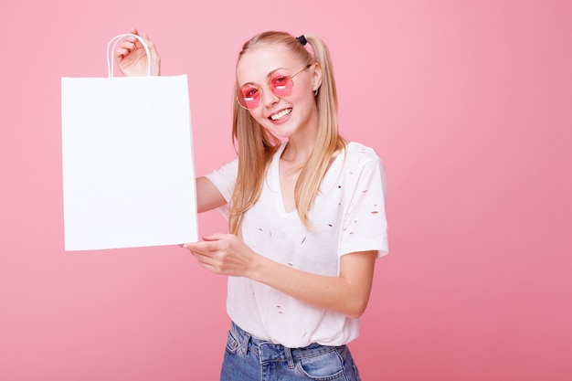 Jonge vrouw houdt witte papieren zak in haar handen op roze