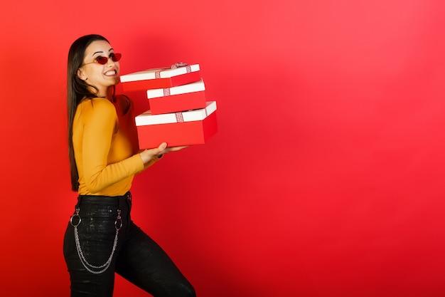 Jonge vrouw houdt zware grote geschenkdozen en staat in de buurt van rode achtergrond