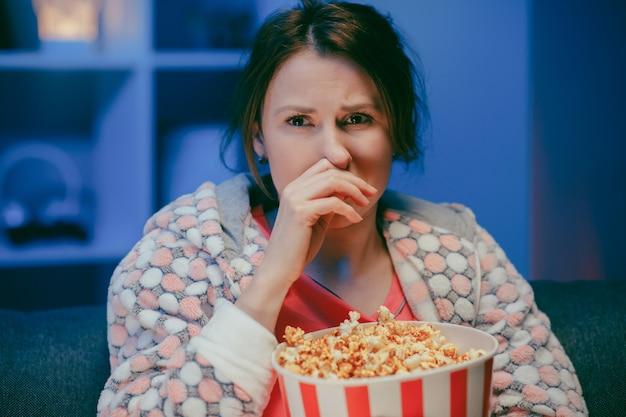 Jonge vrouw huilen tijdens het kijken naar een zeer bewegende film met popcorn 's nachts