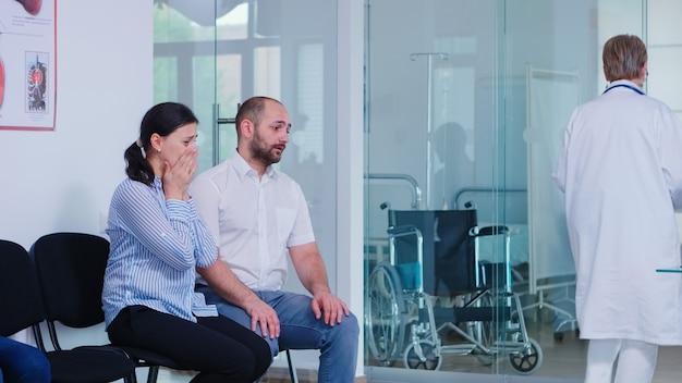 Jonge vrouw huilt na het horen van slecht nieuws van de dokter in de wachtkamer van het ziekenhuis. arts die ongunstige testresultaten geeft. beklemtoonde man en vrouw tijdens doktersafspraak.