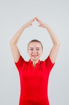 Jonge vrouw huis dak gebaar boven het hoofd in rood t-shirt maken en vrolijk kijken