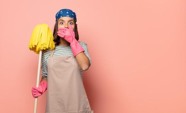 Jonge vrouw huishoudster die mond bedekt met handen met een geschokte, verbaasde uitdrukking, een geheim houdt of oeps zegt saying