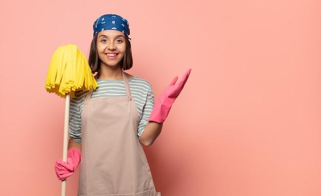 Jonge vrouw huishoudster die zich gelukkig, verrast en opgewekt voelt, glimlachend met een positieve houding