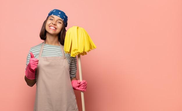 Jonge vrouw huishoudster die zich trots, zorgeloos, zelfverzekerd en gelukkig voelt, positief glimlacht met omhoog duimen