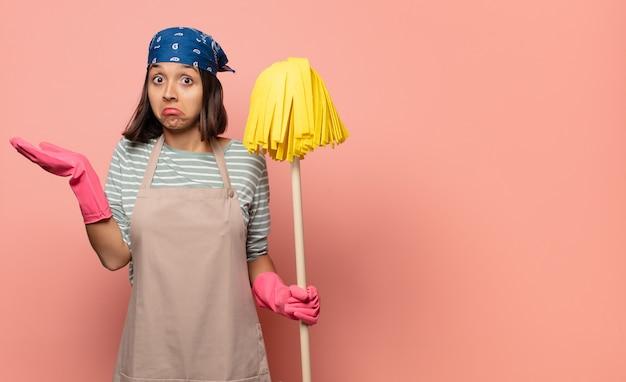 Jonge vrouw huishoudster die zich verward en verward voelt, twijfelt, weegt of verschillende opties kiest met grappige uitdrukking