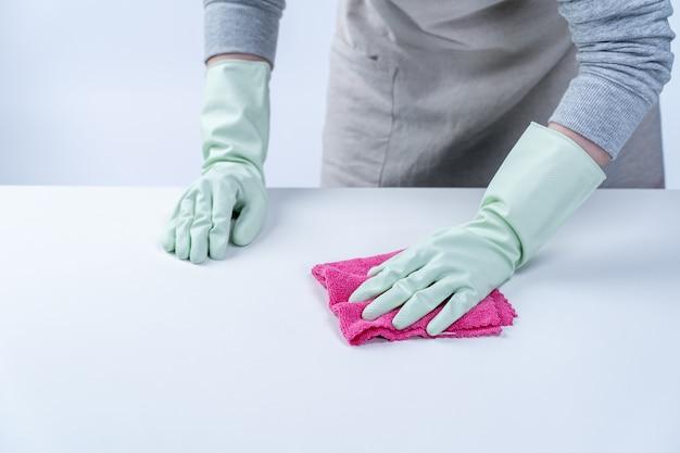 Jonge vrouw huishoudster in schort is schoonvegen tafeloppervlak met natte doek sproeien fles reiniger om verspreiding van de ziekte te voorkomen