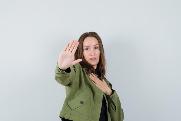 Jonge vrouw iets met handgebaar in groene jas afwijzen en voorzichtig kijken. vooraanzicht.