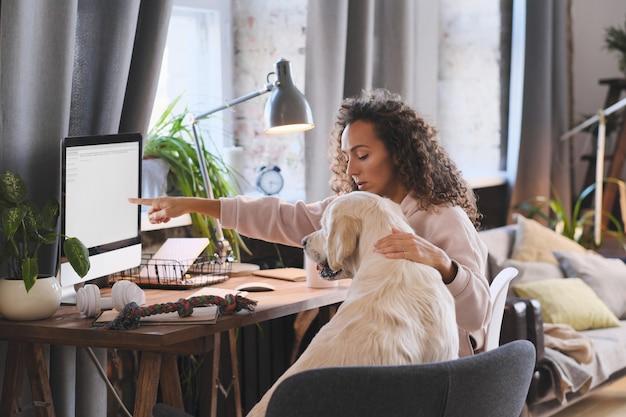 Jonge vrouw iets tonen aan haar hond op de computer tijdens online gesprek thuis