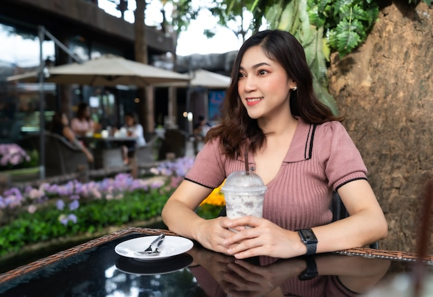 Jonge vrouw ijskoude melk frappe drinken in een café