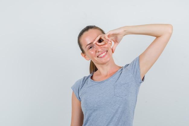 Jonge vrouw imiteert bril met vingers in grijs t-shirt en kijkt grappig, vooraanzicht.