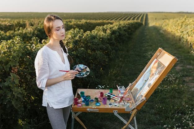 Jonge vrouw in aard het schilderen