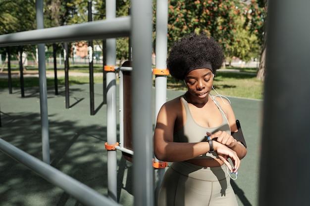 Jonge vrouw in activewear kijkt naar smartwatch om haar pols