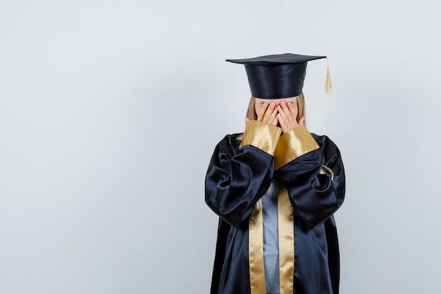 Jonge vrouw in afgestudeerd uniform dat gezicht bedekt met handen en er depressief uitziet