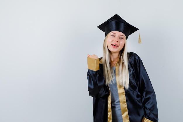 Jonge vrouw in afgestudeerd uniform die winnaargebaar toont en er zelfverzekerd uitziet