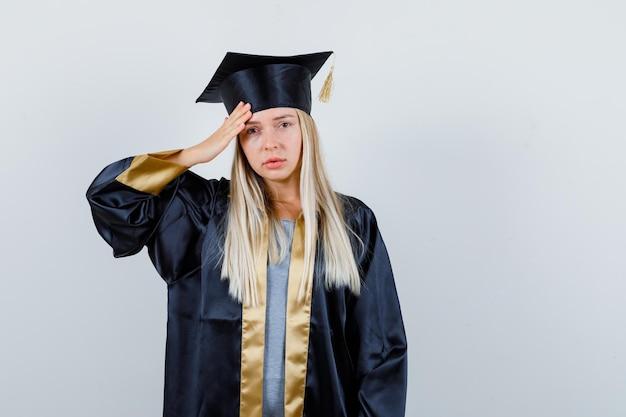 Jonge vrouw in afgestudeerd uniform met sterke hoofdpijn en onwel,