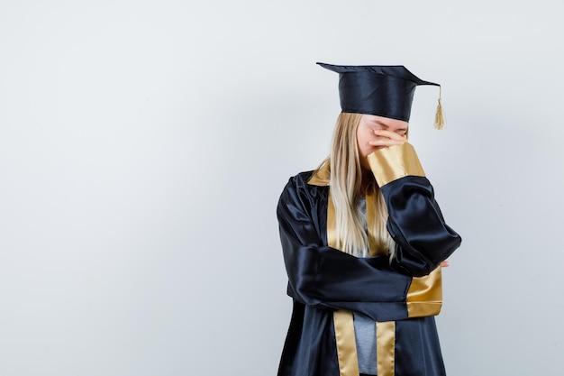 Jonge vrouw in afgestudeerd uniform wrijft over oog en neus en ziet er bedroefd uit