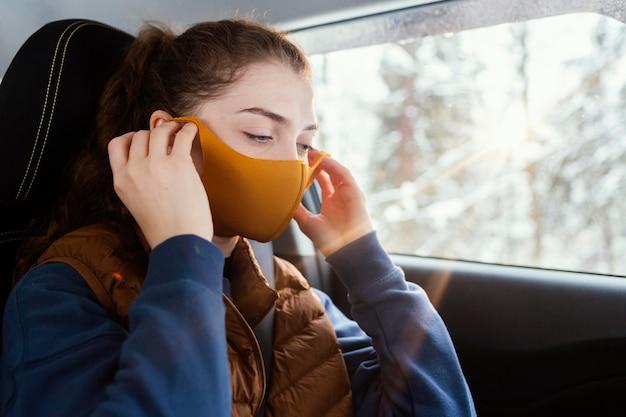 Jonge vrouw in auto die masker draagt