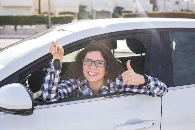 Jonge vrouw in auto verschijnt duimen en sleutel.