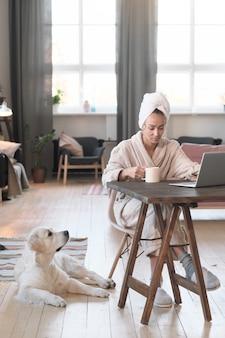 Jonge vrouw in badjas aan de tafel zitten en online met laptop thuis werken