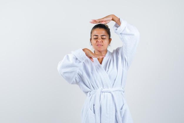 Jonge vrouw in badjas die framegebaar maakt en er schattig uitziet