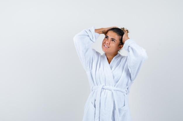 Jonge vrouw in badjas die handen op het hoofd houdt en zich afvraagt