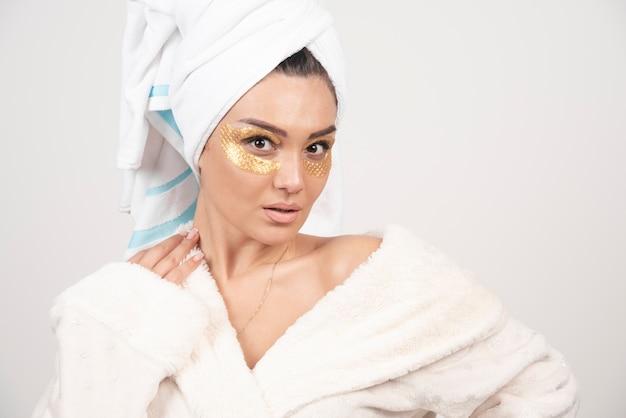Jonge vrouw in badjas en cosmetische ooglapjes poseren.