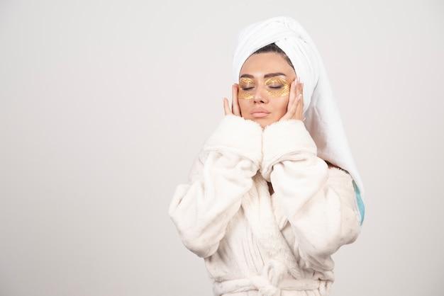 Jonge vrouw in badjas en cosmetische ooglapjes wat betreft haar gezicht.