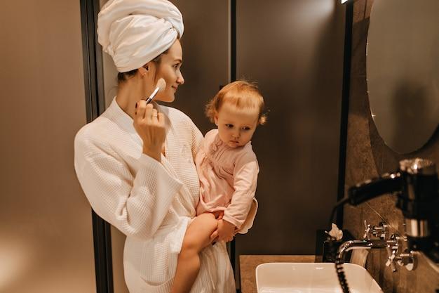 Jonge vrouw in badjas houdt blonde dochter en doet haar eigen make-up, in badkamerspiegel kijken.