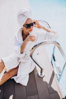 Jonge vrouw in badjas koffie drinken bij het zwembad