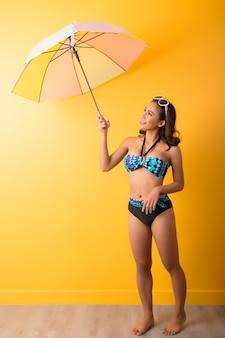 Jonge vrouw in badkleding geïsoleerd dan geel