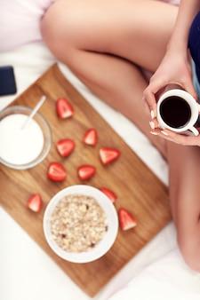 Jonge vrouw in bed met ontbijt en smartphone